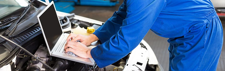 mechanic using a laptop for diagnostic testing on a vehicle